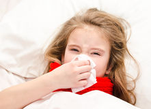 Little girl lying in the bed and blowing her nose Stock Images