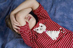 Little girl lying on bed closing face Stock Image