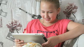 Little girl lying on the bed with a digital tablet stock video