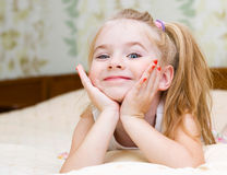 Little girl lying on the bed. Happy little girl lying on the bed Royalty Free Stock Photos