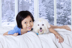 Little girl lying on bed with her puppy. Photo of a cute little girl lying on bedroom while hugging her puppy and smiling at the camera with winter background on Stock Photos