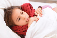 Little girl lying in bed Stock Photos