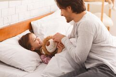 Little girl lying in bed in morning, hugging teddy bear