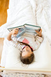 Little girl lying at bed in morning and reading big book Stock Photos