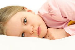 A little girl lying in bed with open eyes. Watching into the camera Stock Photos