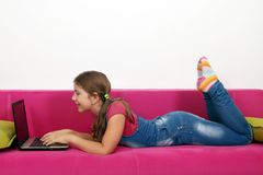 Little girl lying in bed and playing laptop Stock Photography