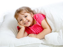 Little girl lying in bed Royalty Free Stock Photos