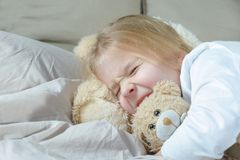 The little girl is lying in bed and pretending to be asleep. A child holds tightly a teddy bear. stock photography