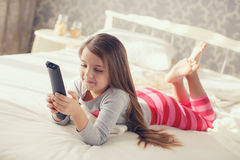 Little girl lying in bed with a remote control TV Royalty Free Stock Images