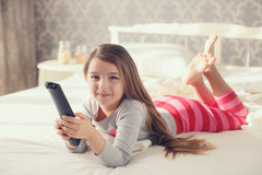 Little girl lying in bed with a remote control TV Royalty Free Stock Image