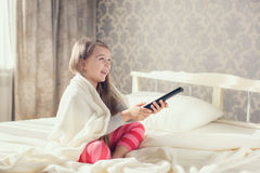 Little girl lying in bed with a remote control TV Stock Photography