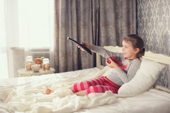 Little girl lying in bed with a remote control TV Royalty Free Stock Photos