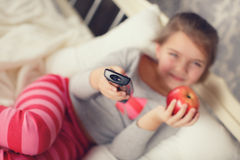 Little girl lying in bed with a remote control TV Stock Photos