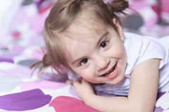 Little girl lying on bed in room Royalty Free Stock Images
