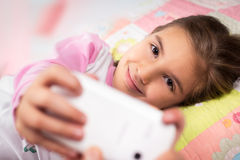Little girl lying in bed with smartphone at home Stock Image