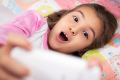 Little girl lying in bed with smartphone at home Stock Photos