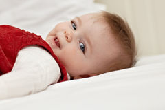Little girl lying on bed and smiling Royalty Free Stock Photography