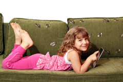 Little girl lying on bed with tablet Royalty Free Stock Photography