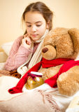 Little girl lying in bed with teddy bear with honey jar Stock Photos