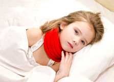 Little girl lying in the bed with thermometer Royalty Free Stock Photos