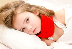 Little girl lying in the bed with thermometer Royalty Free Stock Image