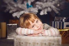 Little girl lying on big present near the christmas tree Stock Photos