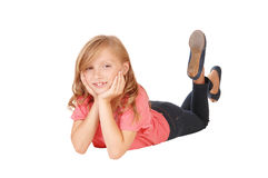 Little girl lying. A blond little girl in a pink sweater lying on the floor on her stomach Stock Photography