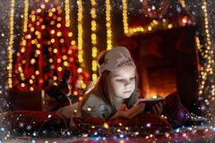 Little girl lying in carpet with presents around using tablet on stock photography
