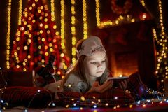 Little girl lying in carpet with presents around using tablet on stock photos