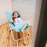 Little girl lying on a chaise lounge Stock Image
