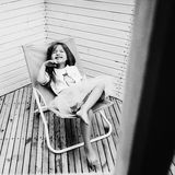 Little girl lying on a chaise lounge.  royalty free stock image