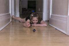 Little girl lying on corridor hardwood floor playing with small and large glass marbles. Horizontal shot of beautiful smiling little girl lying on corridor Royalty Free Stock Photo