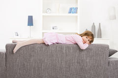 Little girl lying on couch Royalty Free Stock Photography