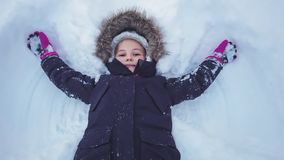 Girl lying in a deep snow stock image
