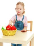 Little girl lying disassembled in a fruit basket. Stock Image