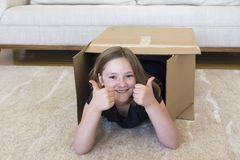 Little girl lying down in brown cardboard box making a double thumbs up sign stock images