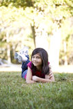 Little girl lying down on grass Stock Image