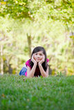 Little girl lying down on grass Stock Images