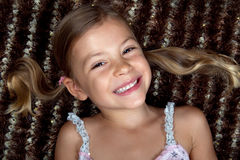 Little girl lying down on a rug and smiling Stock Photography