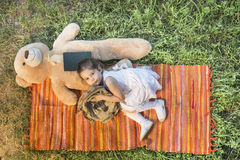 Little girl lying down with teddy bear on the picnic blanket. Adorable little girl with backpack lying down with teddy bear on the picnic blanket outdoor in a Royalty Free Stock Photos