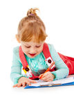 The little girl lying and draw Stock Images