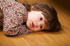 Little girl lying on floor Stock Images