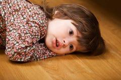 Little girl lying on floor Stock Images