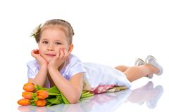 A little girl is lying on the floor with a bouquet of tulips. Stock Photo