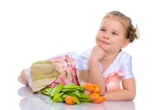 A little girl is lying on the floor with a bouquet of tulips. Stock Image