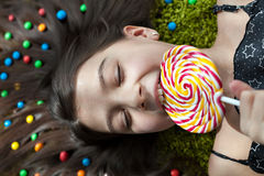 Little girl lying on the floor and eating candy Stock Photos