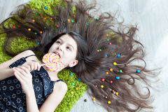 Little girl lying on the floor and eating candy Stock Image