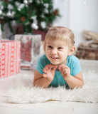 Little girl lying on floor near Christmas tree. stock photography