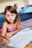 A little girl lying on the floor while studying Royalty Free Stock Image