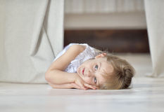 Little girl lying on the floor Stock Images